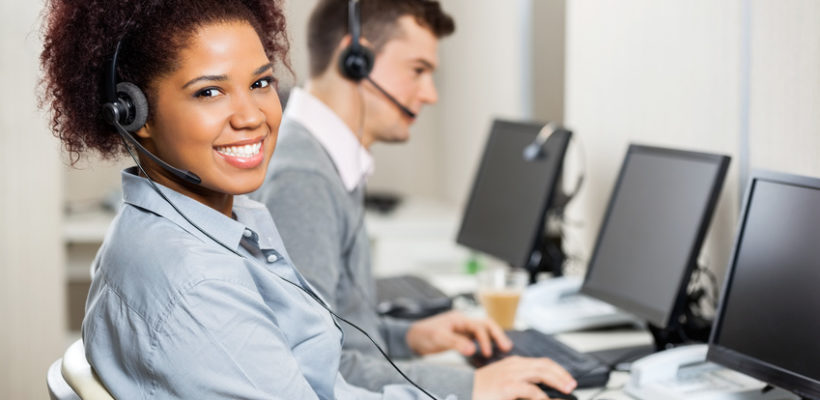 Portrait of smiling female customer service representative with male colleague working in office